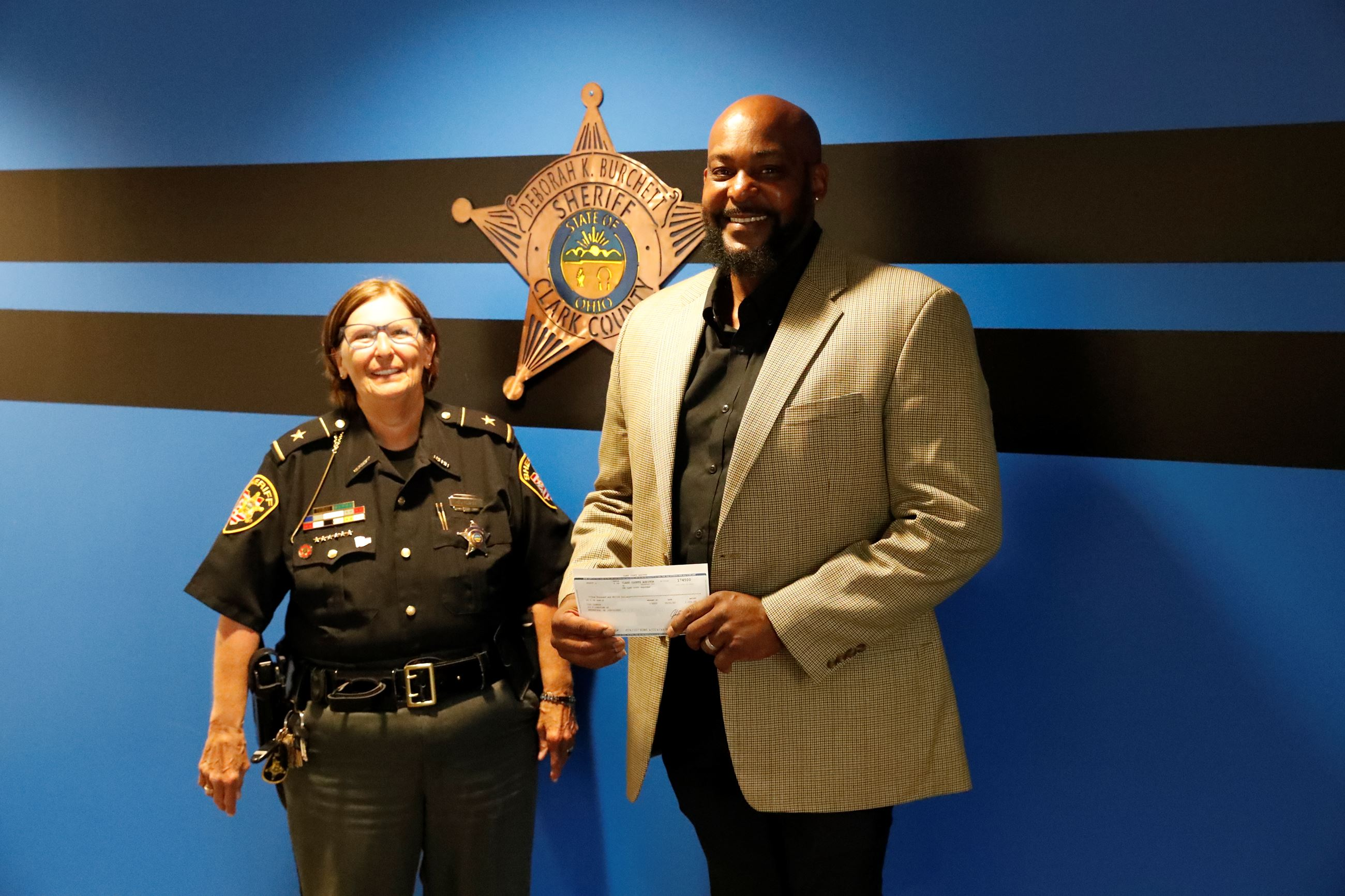 Sheriff Deb Burchett presents a check to Stephen Massey of CitiLookout.