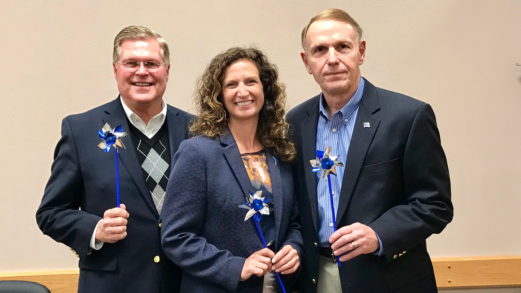 Clark County Commissioners Lowell McGlothin, Melanie Flax Wilt and Rick Lohnes hold pinwheels in support of Child Abuse Awareness Month.